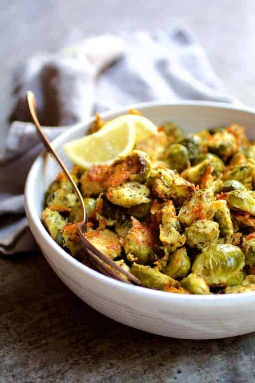 Lemon Parmesan Crusted Brussels Sprouts - Hero shot in white bowl with serving spoon
