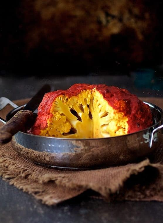 Brined Whole Roasted Tandoori Cauliflower - Hero shot in metal roasting pan with wedge removed to show interior of cauliflower