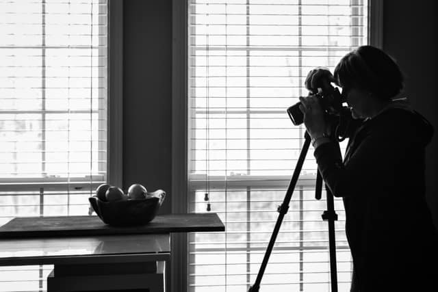 Photo of Carol Borchardt taking a food photo in front of window.