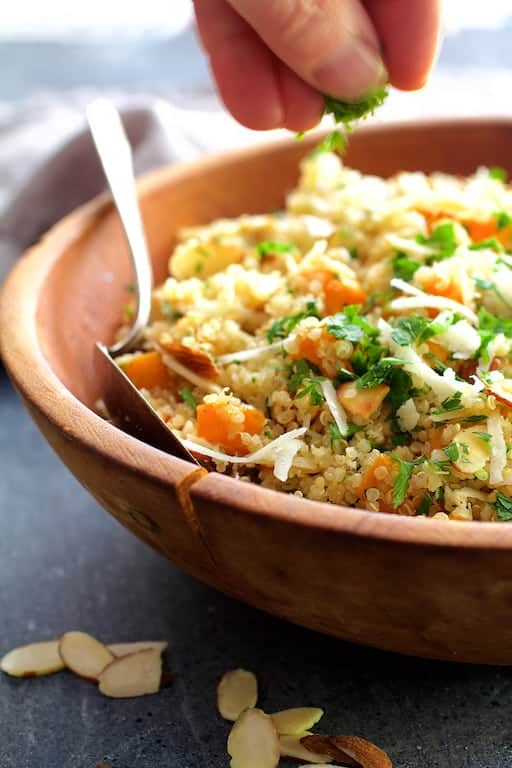 Lemony Quinoa with Butternut Squash, Almonds and Parmesan Cheese - Parsley being sprinkled over dish