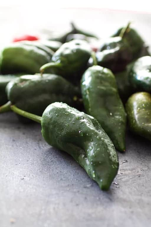 A pile of fresh poblano peppers after being washed