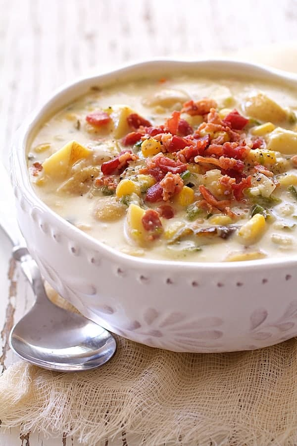 Close-up photo of Roasted Poblano, Corn and Potato Chowder with Bacon and Gouda Cheese in white bowl with spoon on the side.