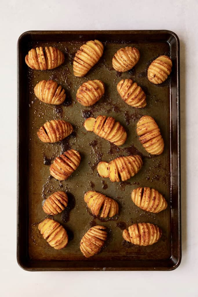 Overhead shot of Hasselbacked potatoes on baking sheet after being roasted