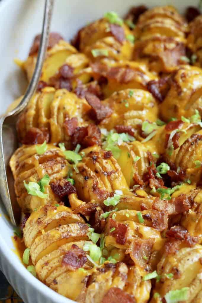 Baby Hasselback Potato Bake with Cheddar and Bacon - Close-up shot in white baking dish with serving spoon