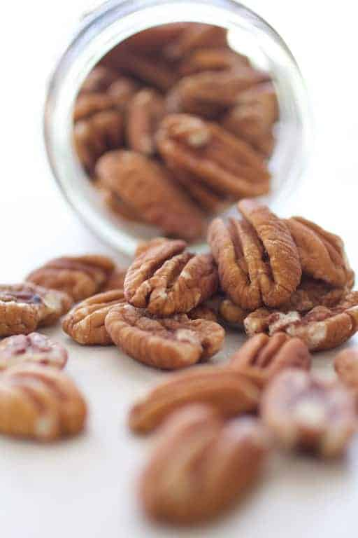 Pecans spilling out of glass jar