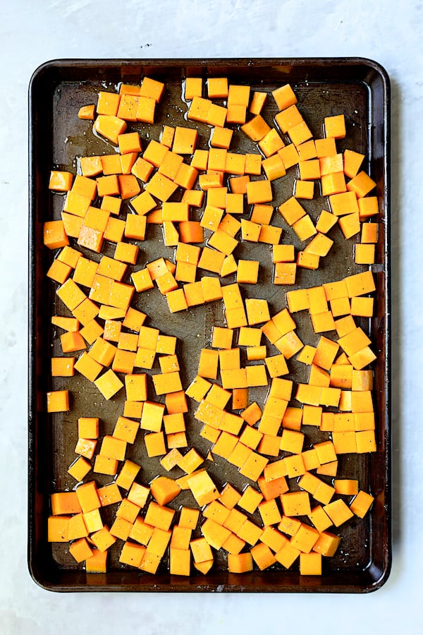 Overhead shot of cubed butternut squash on baking sheet