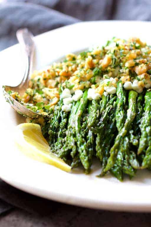 Roasted Asparagus with Goat Cheese and Walnut Lemon Gremolata - Straight-on shot of dish on white platter