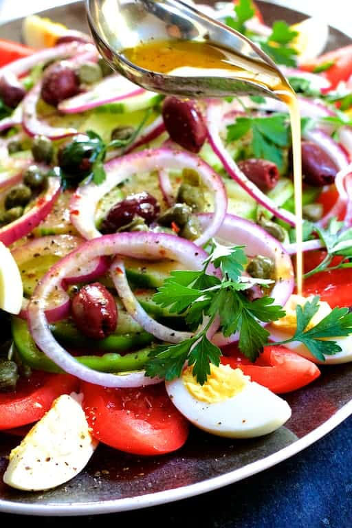 Tunisian Salad Platter (Assiette Tunisienne) - Dressing being drizzled over salad from silver serving spoon