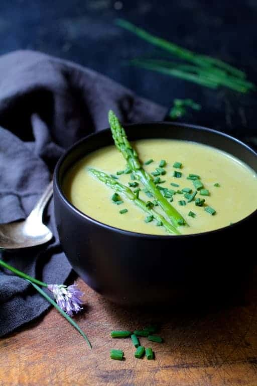 Cream of Asparagus and Leek Soup with Curry - Hero shot of soup in black bowl garnished with asparagus spears and fresh chives