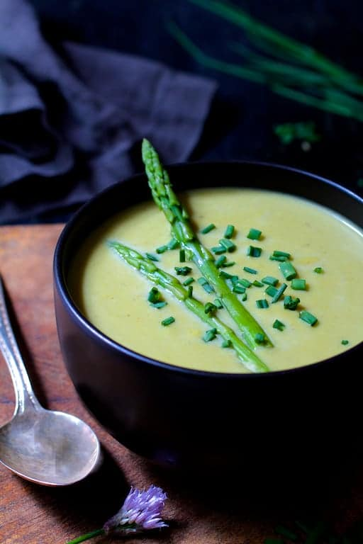 Cream of Asparagus and Leek Soup with Curry close-up with chives and chive blossom