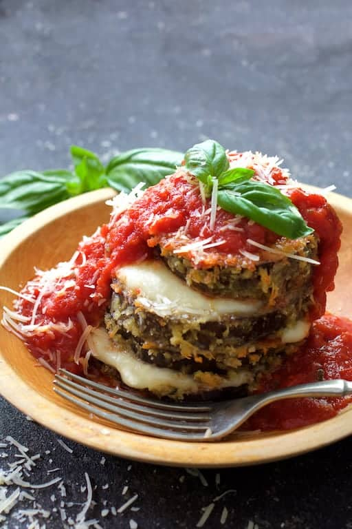 Eggplant Parmesan Stacks - Close-up shot of dish in wooden bowl garnished with fresh basil and fork ready to eat