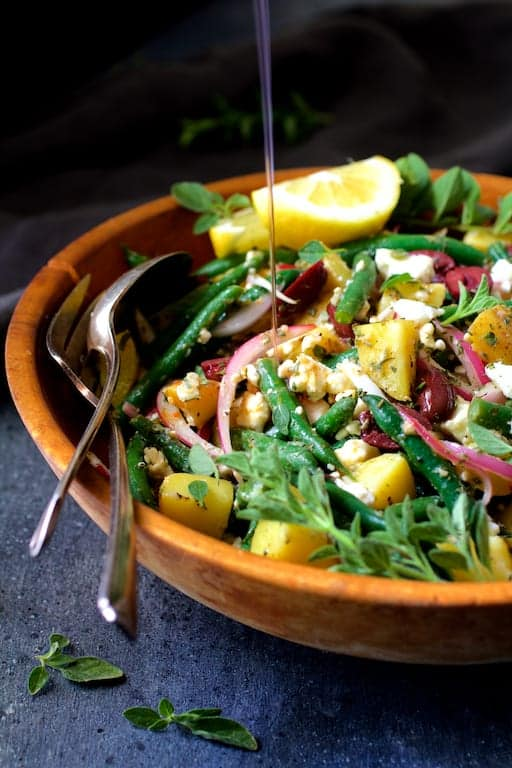 Potato Green Bean Salad with Olives and Feta Cheese - Salad in wood serving bowl being drizzled with dressing