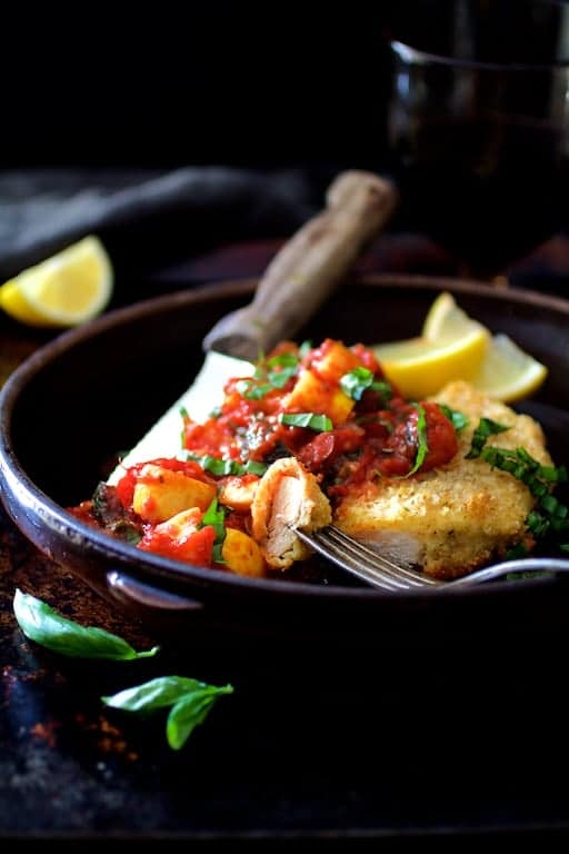 Chicken Scallopini with Roasted Vegetable Ratatouille - Straight-on shot in clay dish with a piece on a fork