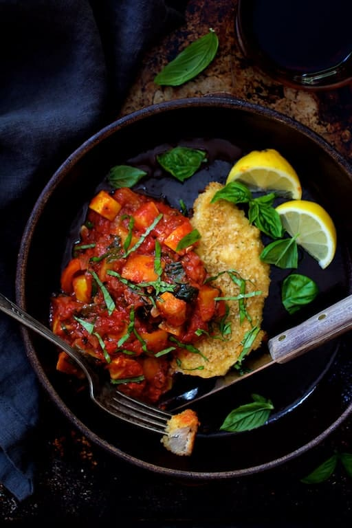 Chicken Scallopini with Roasted Vegetable Ratatouille - Overhead shot of ratatouille in clay dish garnished with fresh basil and lemon wedges