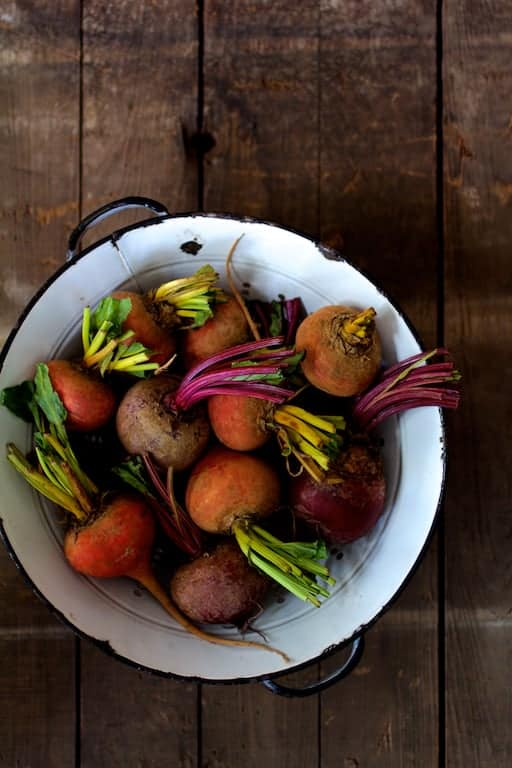Roasted Hasselback Beets with Dill Dressing - Overhead shot of whole raw beets in antique white colander on wooden background