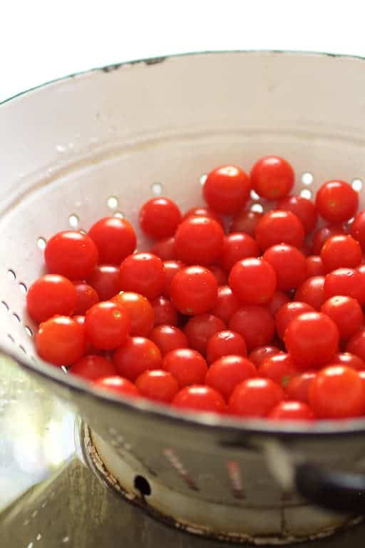 Caprese Pizza Pasta Salad - Antique white colander filled with cherry tomatoes freshly washed