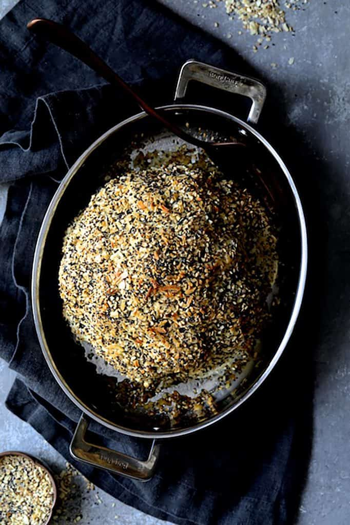 Everything Bagel Spice Whole Roasted Cauliflower - Overhead shot of roasted cauliflower in roasting pan on an angle on dark gray towel with everything bagel spice scattered around