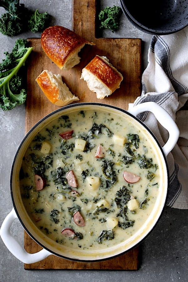Creamy Potato Kielbasa and Kale Soup - Overhead shot of soup in white Dutch oven with bread and fresh kale