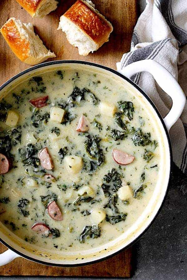Creamy Potato Kielbasa and Kale Soup - Overhead close-up shot of soup in white Dutch oven