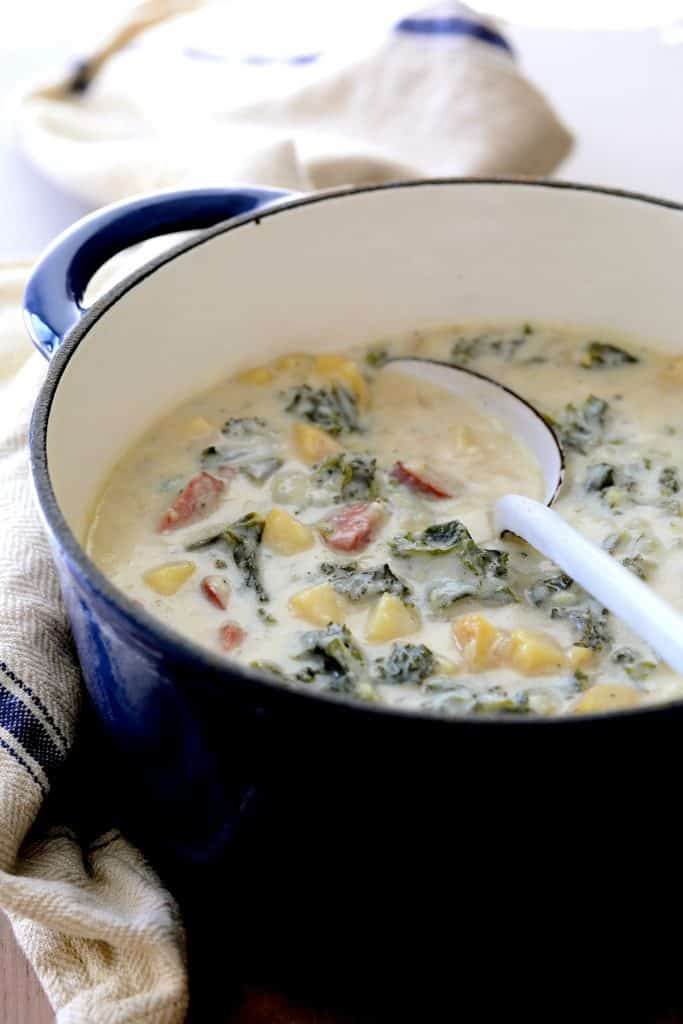 Creamy Potato Kielbasa and Kale Soup - Soup in blue Dutch oven with white serving spoon