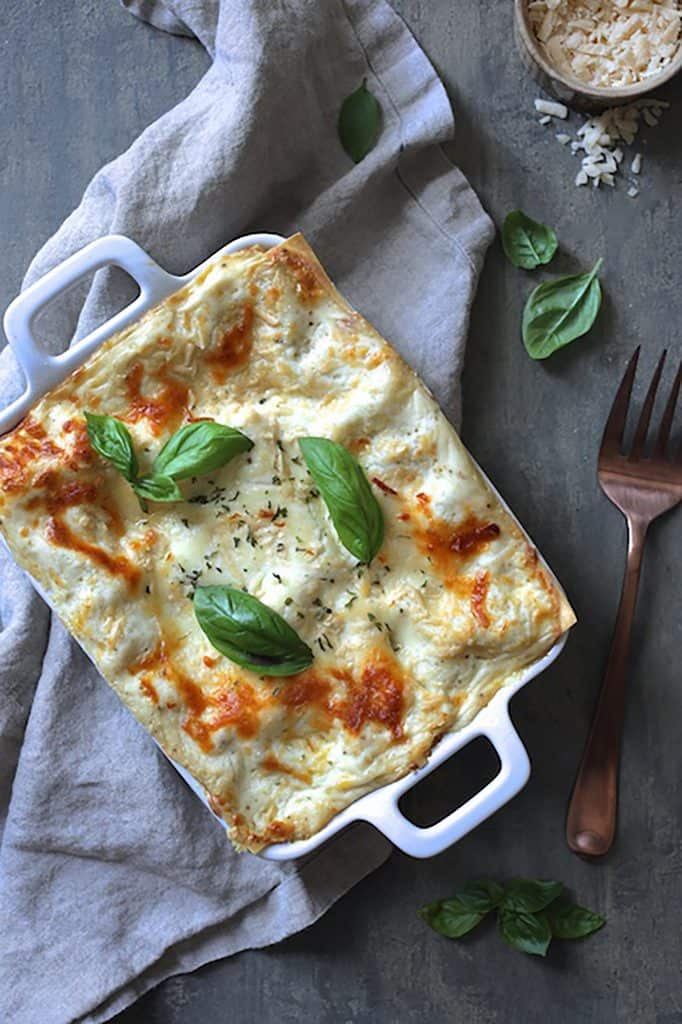 Lasagna with Pesto Green Beans and Potatoes - Overhead shot of lasagna garnished with fresh basil on gray background with serving fork