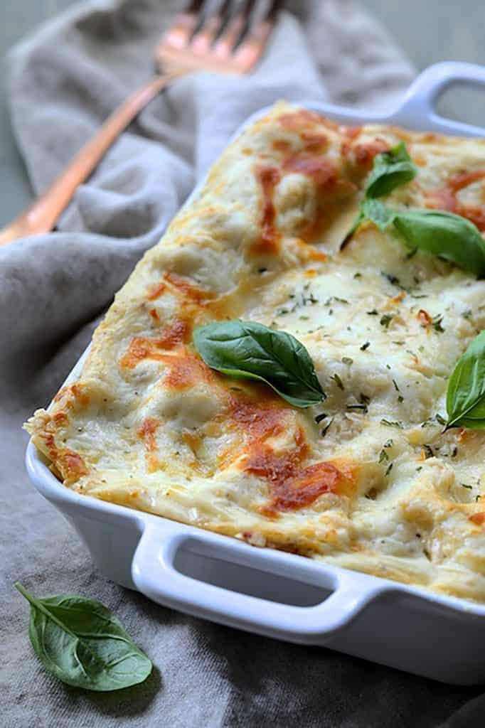 Lasagna with Pesto Green Beans and Potatoes - Close-up shot of lasagna in white baking dish garnished with fresh basil