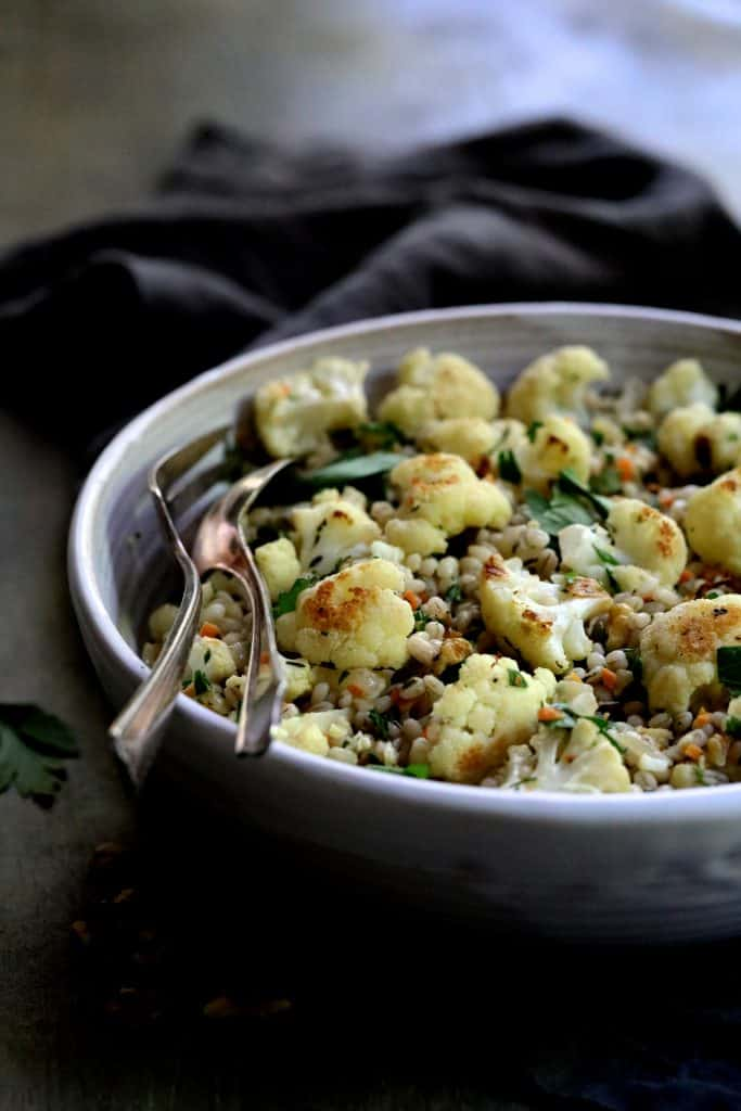 Roasted Cauliflower and Barley Pilaf in bowl with serving spoons and gray napkin.