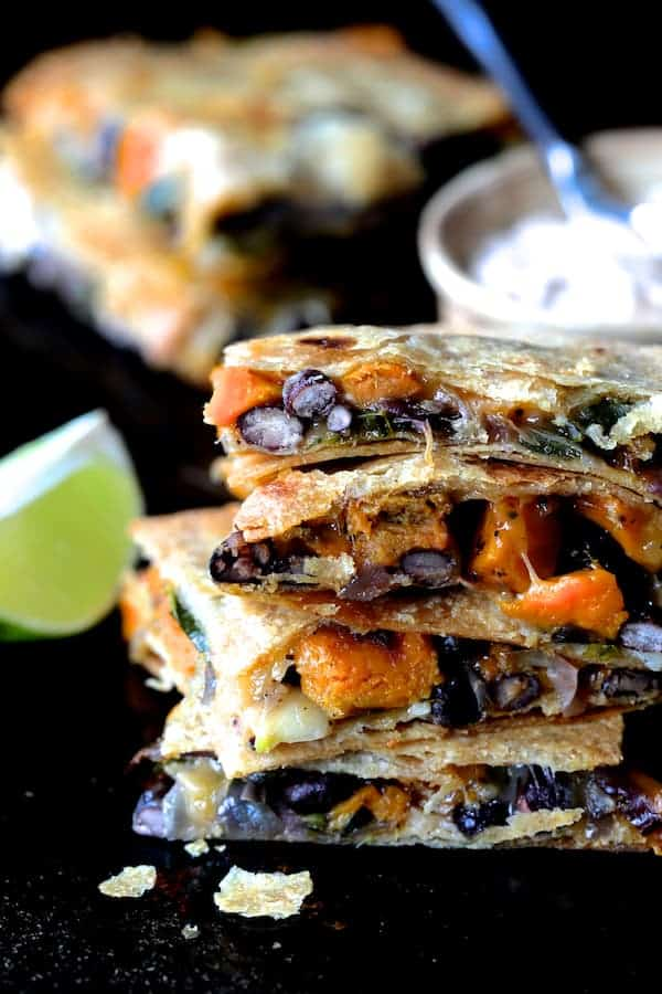Sheet Pan Quesadillas with Sweet Potatoes, Poblanos and Black Beans with Chipotle Sour Cream close-up shot
