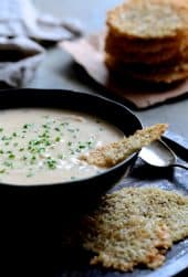 Creamy White Bean, Rutabaga and Roasted Garlic Soup with Quinoa Parmesan Crisps hero shot with stack of quinoa crisps garnished with fresh chives