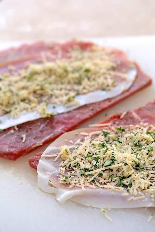 Beef Braciole being assembled. Thin slices of beef round topped with prosciutto and a parmesan breadcrumb combination.