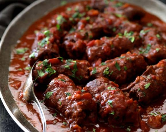 Beef Braciole on gray-rimmed platter ready to serve with serving fork