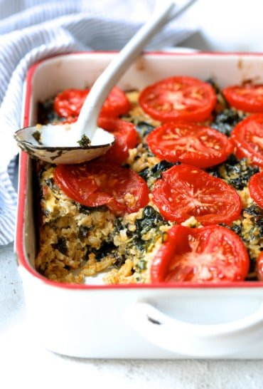 Brown Rice, Cheddar and Kale Casserole on white background with striped towel on wood trivet with white spoon with some served