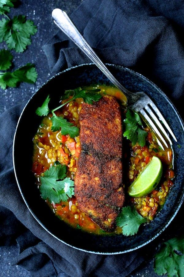 Photo of one serving of Indian Spiced Sea Bass with Braised Red Lentils in bowl with cilantro sprigs and lime wedges.