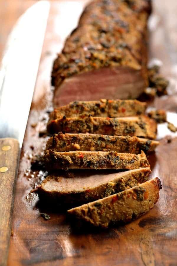 Photo of sliced Cuban Style Mojo Marinated Pork Tenderloin sliced on wooded cutting board.
