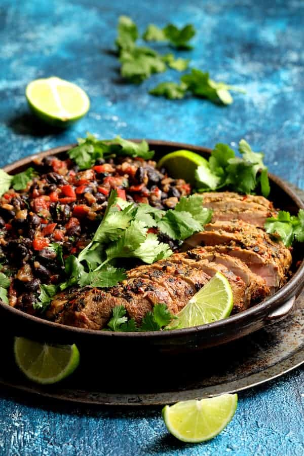 Photo of Cuban Style Mojo Marinated Pork Tenderloin with Black Beans on bright blue background.