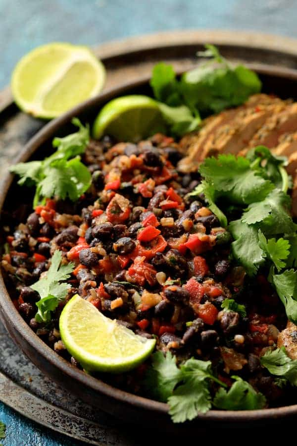 Close-up photo of black beans garnished with lime wedges.