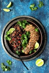 Cuban Style Mojo Marinated Pork Tenderloin with Black Beans - Overhead shot on blue background