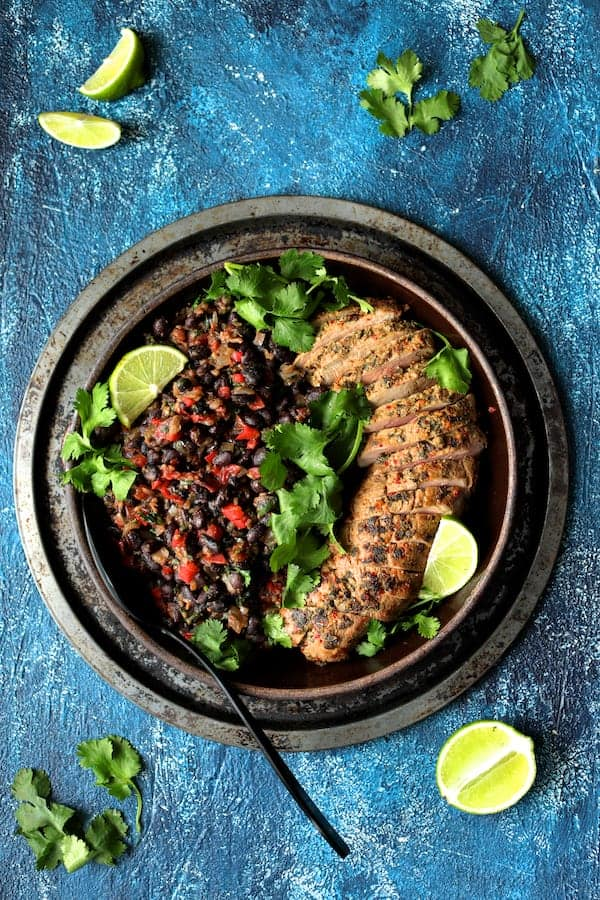Cuban Style Mojo Marinated Pork Tenderloin with Black Beans - Overhead shot on blue background