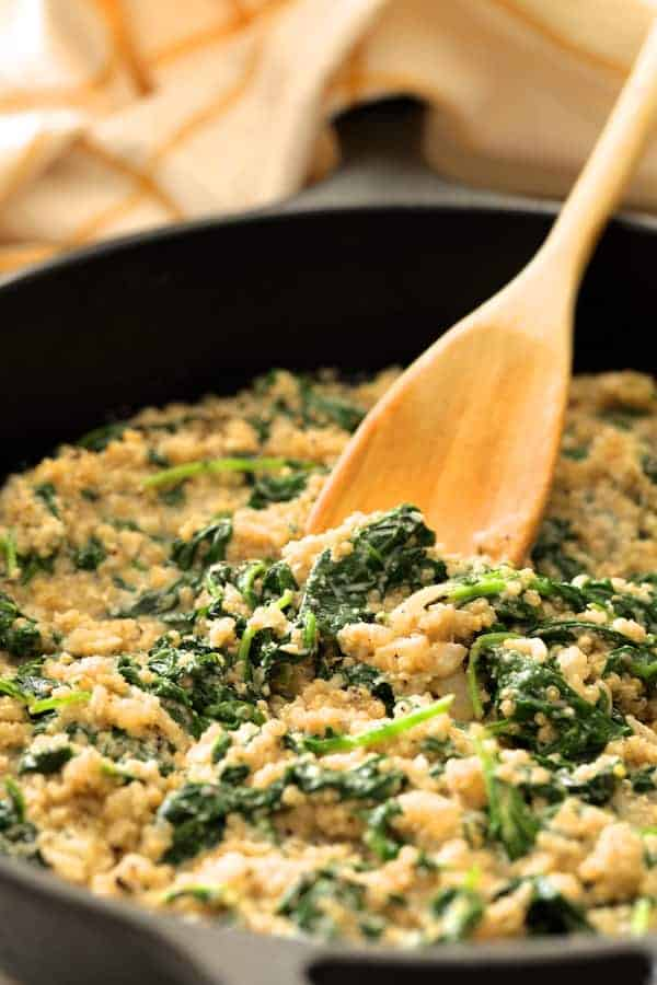 Photo of baby kale quinotto in skillet being stirred with wooden spoon.