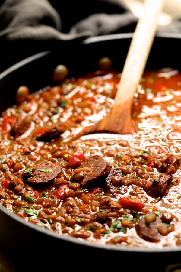 Soupy Spanish Lentils with Chorizo and Manchego Toast cooking in pot with wooden spoon