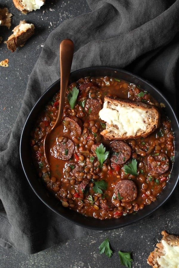 Photo of Soupy Spanish Lentils with Chorizo and Manchego Toast on gray background with gray towel.