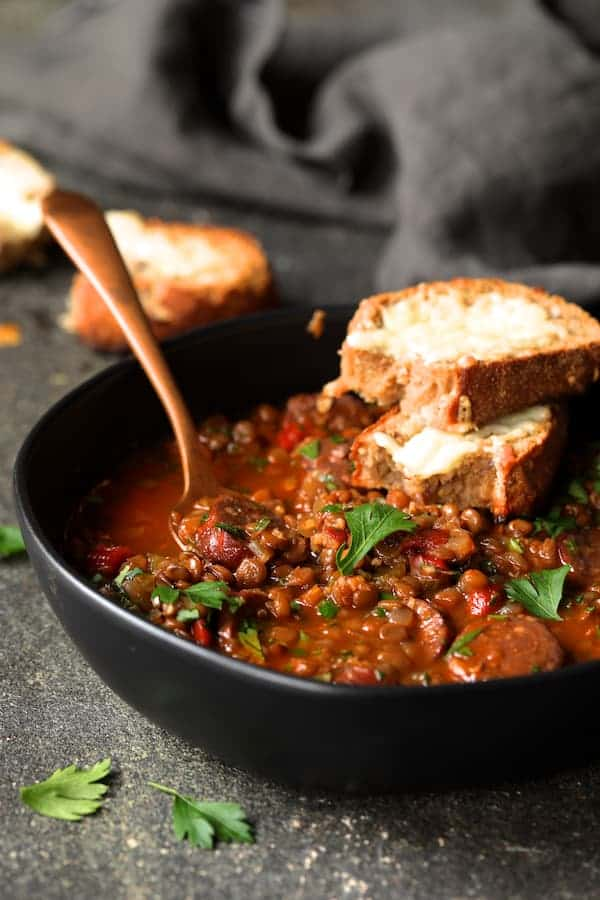 Photo of one serving of Soupy Spanish Lentils with Chorizo and Manchego Toast garnished with fresh parsley.