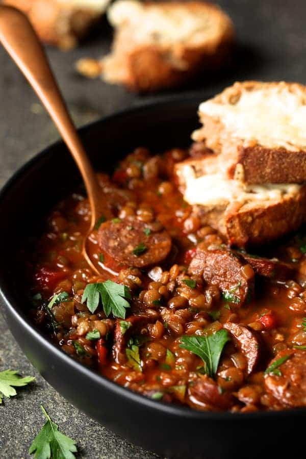 Soupy Spanish Lentils with Chorizo and Manchego Toast extreme close-up in black bowl with gray napkin