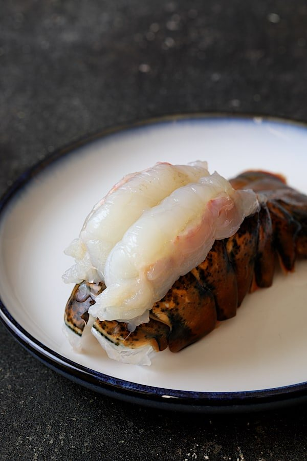 Steak au Poivre and Broiled Lobster Tail - Photo of uncooked lobster tail with meat on top of shell