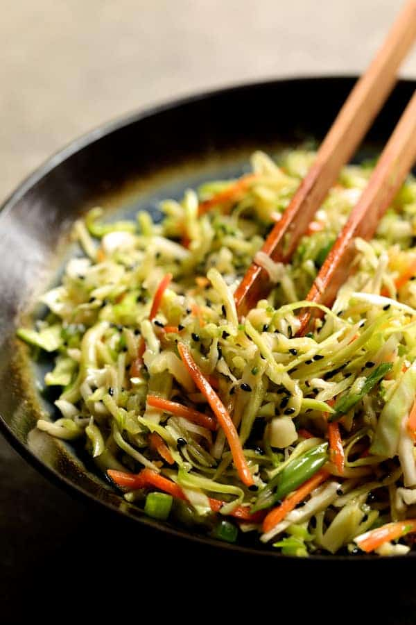 Vegan Korean Tofu Lettuce Wraps with Tahini Gochujang Sauce and Spicy Slaw - Photo of spicy slaw in bowl with tongs