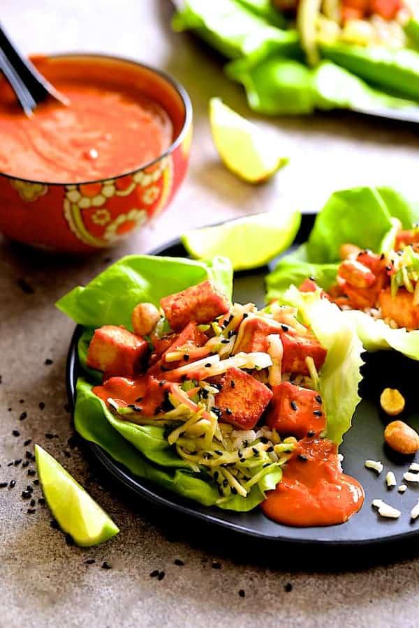 Vegan Korean Tofu Lettuce Wraps with Tahini Gochujang Sauce and Spicy Slaw - Hero shot of dish on black plate
