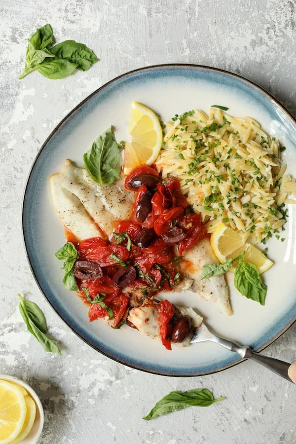 Photo of Baked Fish with Cherry Tomato Olive Sauce and Lemon Chive Asiago Orzo on blue-rimmed plate with a forkful cut from the fish.