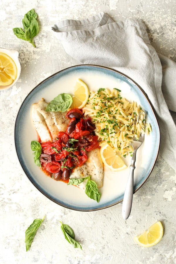 Photo of Baked Fish with Cherry Tomato and Olive Sauce and Lemon Chive Asiago Orzo on blue-rimmed plate garnished with fresh basil.