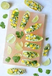Crab Mango and Avocado Salad with Chile Lime Dressing in Endive - Overhead hero shot on pink salt block