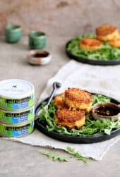 Tuna Kimchi Cakes with Soy Ginger Dipping Sauce hero shot with three cans of tuna stacked to the left of the tuna cakes